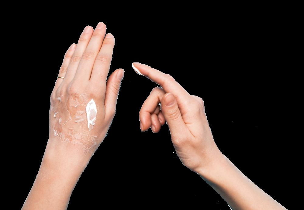 Frau cremt sich die Hand mit Hyaluronsäure ein